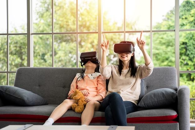 Kind und frau mit virtual-reality-headset lächeln, während sie zu hause auf dem sofa sitzen