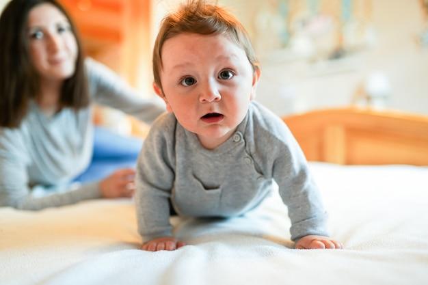 Kind und mutter auf dem bett. mutter und baby, die im sonnigen schlafzimmer spielen