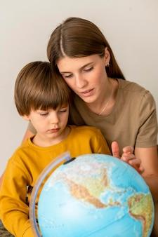Kind und mutter betrachten globus zusammen