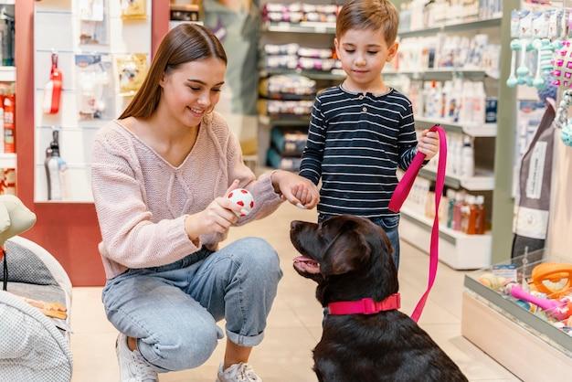 Kind und mutter in der tierhandlung mit ihrem hund