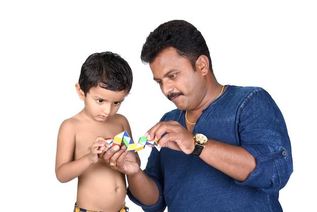 Kind und sein vater spielen mit spielzeug. kinderjunge und vater spielen mit spielzeug auf weißem hintergrund.