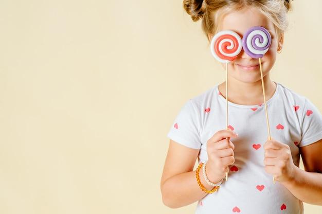 Kind und süßigkeiten. ein kleines mädchen hält süßigkeiten in ihren händen.