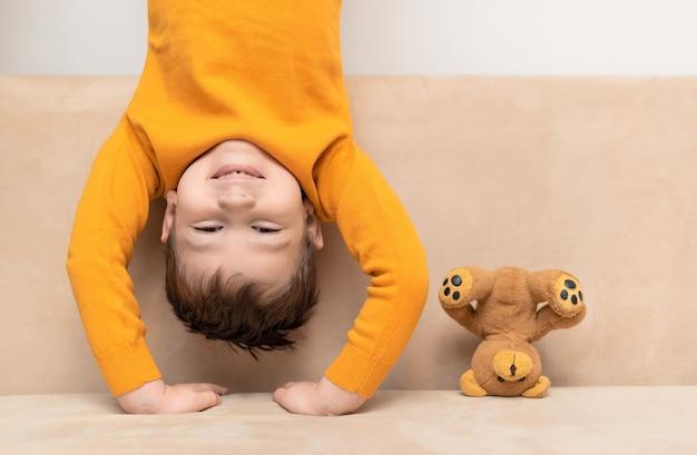 Kind und teddybär stehen auf ihren köpfen auf der couch. eine andere sichtweise, kindheitskonzept.