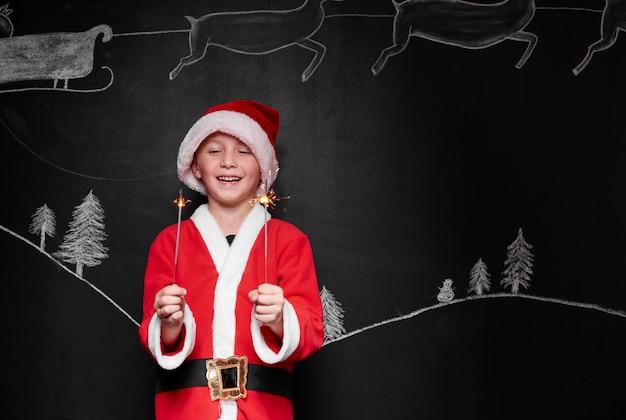 Kind verkleidet als weihnachtsmann, der eine wunderkerze genießt