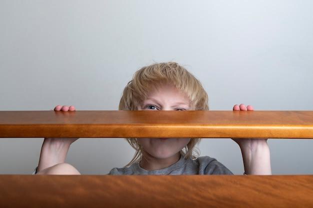 Kind versteckt sich hinter dem geländer. gewalt in der familie. häusliche gewalt. missbrauch