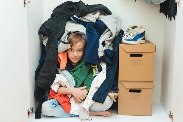 Kind versteckt sich unter unordentlichen kleidern im schrank