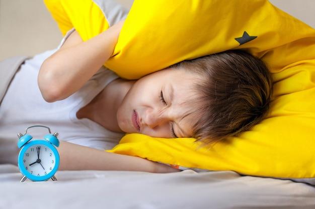 Kind versucht zu schlafen, wenn morgens der wecker klingelt. zeit aufzuwachen.
