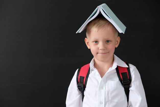 Kind von der grundschule mit buch auf seinem kopf an der tafel