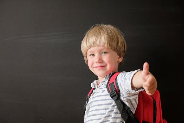 Kind von der grundschule mit tasche an der tafel.