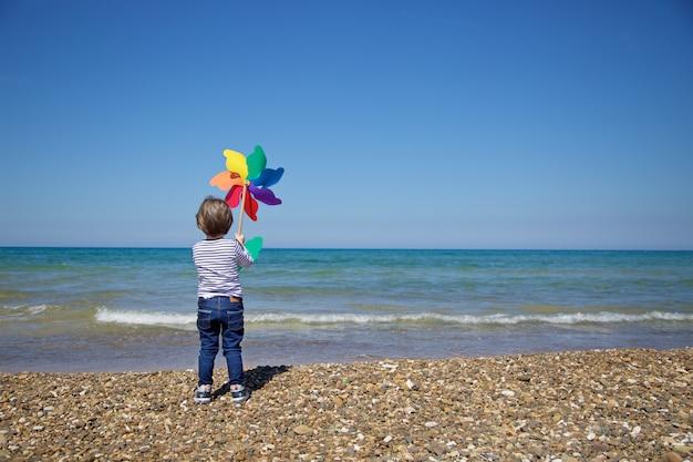 Kind von hinten hält ein buntes windrad vor dem meer