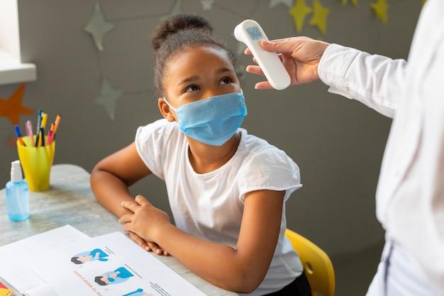 Kind wartet darauf, dass die lehrerin ihre temperatur misst