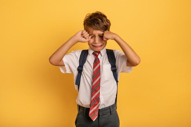 Kind weint, weil es nicht zur schule gehen will. gelber hintergrund