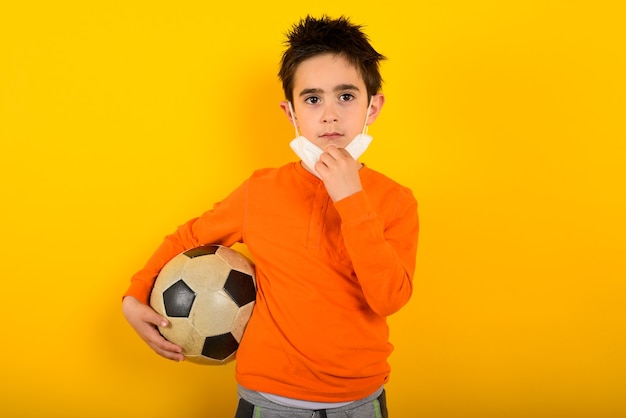 Kind will mit gesichtsmaske für covid-19-coronavirus will fußball auf gelb spielen
