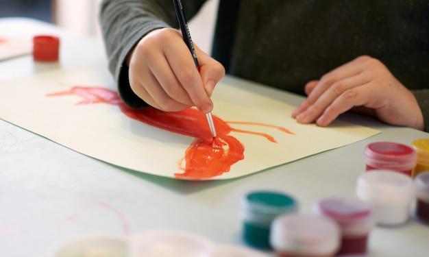 Kind zeichnet ein bild während des online-kunstunterrichts am handy, quarantäne covid-19, selbstisolation, online-bildungskonzept, homeschooling. kinder zu hause, kindergarten geschlossen, homelernen. 6 jahre junge.