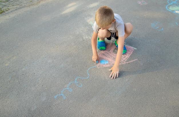 Kind zeichnet ein haus in der kreide auf die pflasterung. tiefenschärfe.