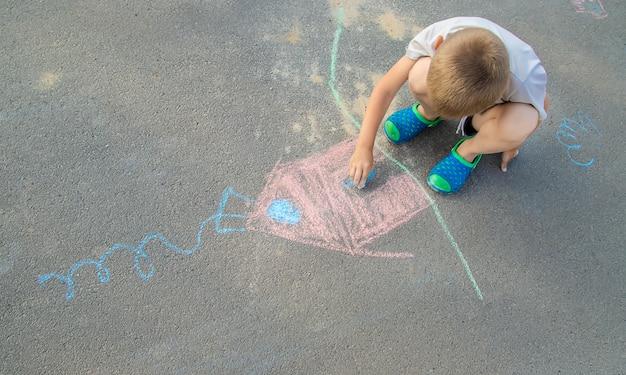 Kind zeichnet ein haus in der kreide auf die pflasterung