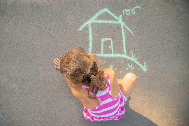 Kind zeichnet ein kreidehaus. selektiver fokus.