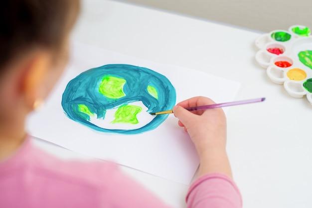 Kind zeichnet einen planeten erde mit einer weltkarte mit aquarellen auf weißem papier. konzept für frieden und tag der erde.