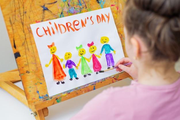 Kind zeichnet glücklichen kindertag