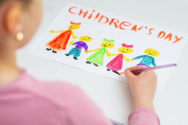 Kind zeichnet glücklichen kindertag.