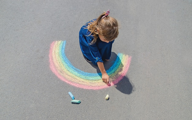 Kind zeichnet mit kreide auf die pflasterung