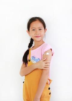 Kind zeigt arm mit klebepflaster, baumwolle von geimpften. asiatisches kleines mädchen mit pflaster auf der schulter von der injektion. behandlung von kinderpflaster. impfkonzept