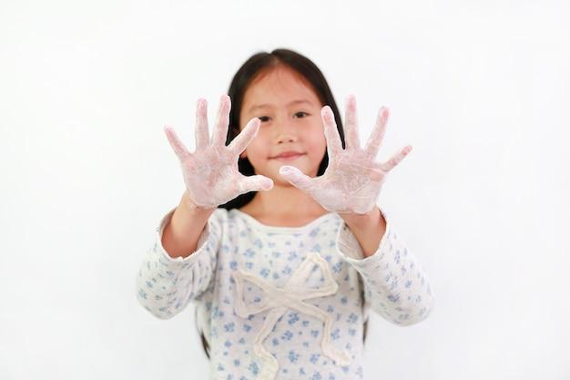 Kind zeigt händewaschen mit wasser und seife auf weißem hintergrund. konzept zur vorbeugung von hygiene und virusinfektionen. fokus auf kinderhände