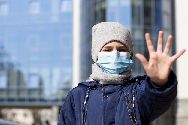 Kind zeigt hand beim tragen der medizinischen maske außerhalb