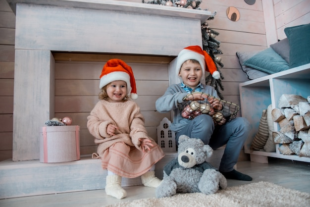 Kinder am kamin zu weihnachten, weiß dekoriert wohnzimmer, wohngebäude. kinder warten auf geschenke vom weihnachtsmann. silvester ist bald