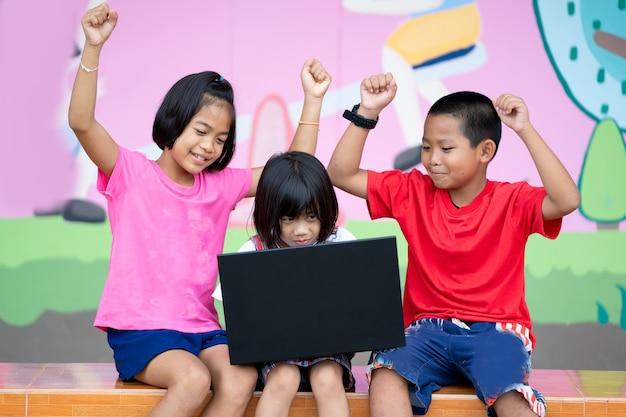 Kinder am laptop in der grundschule