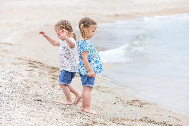 Kinder am meeresstrand. zwillinge gehen am meerwasser entlang.