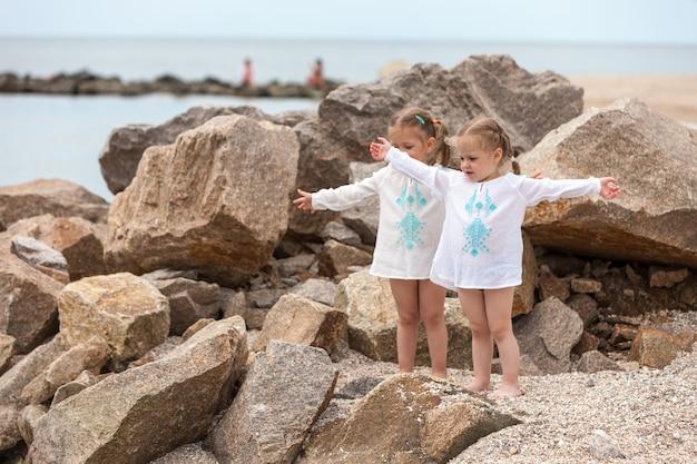 Kinder am meeresstrand. zwillinge stehen gegen steine und meerwasser.