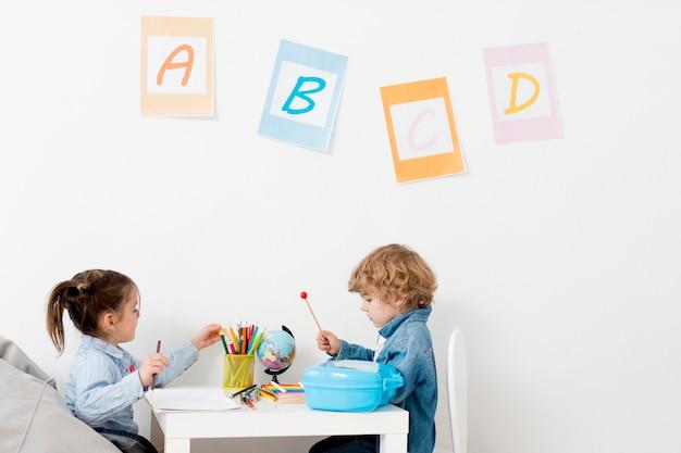 Kinder am schreibtisch spielen zusammen