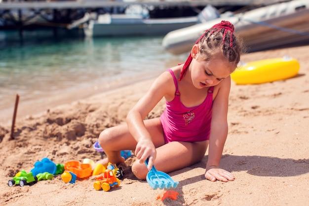Kinder am strand spielen mit sand. kindheits-, urlaubs- und sommerkonzept