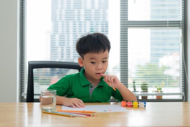 Kinder am studientisch denken. kind, das einen stift und ein notizbuch mit denkender gesichtsaktion hält. junge, der hausaufgaben am studientisch mit denkendem akt macht.