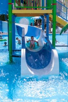 Kinder amüsieren sich im wasserpark und fahren auf wasserrutschen