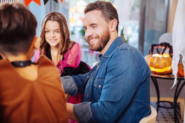 Kinder anschauen. hübscher blauäugiger vater, der jeanshemd trägt und seine kinder betrachtet, die halloween-kostüme tragen