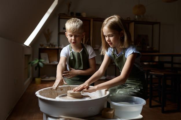 Kinder arbeiten in der werkstatt an einer töpferscheibe