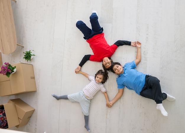 Kinder auf dem boden zusammen in der neuen draufsicht des hauses
