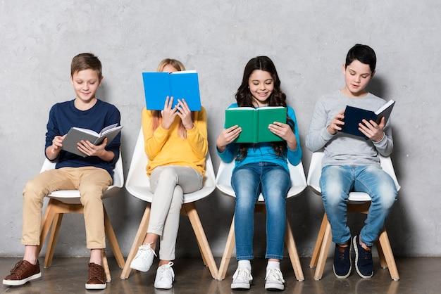Kinder auf stühlen lesen