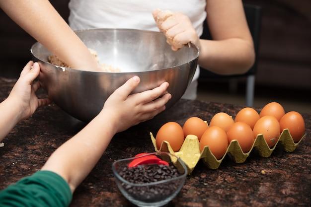 Kinder backen kekse in der hausküche. die hände des nahaufnahmekindes, die plätzchen unter verwendung des plätzchens vorbereiten.
