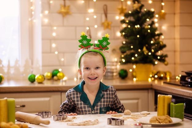 Kinder backen weihnachtslebkuchenplätzchen.
