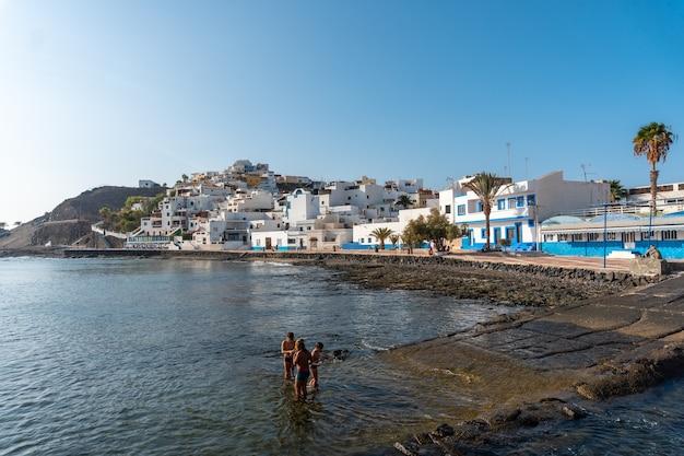 Kinder baden am strand der küstenstadt las playitas, ostküste der insel fuerteventura, kanarische inseln. spanien