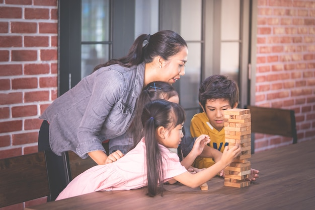 Kinder bauen spielzeugblockturm mit lehrer