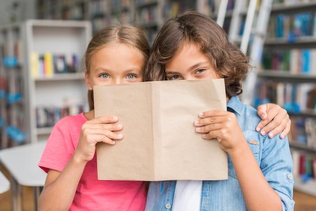 Kinder bedecken ihr gesicht mit einem buch