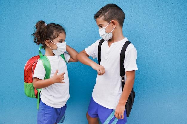Kinder begrüßen sich mit einem ellbogenstoß und tragen eine sicherheitsmaske, während sie wieder zur schule gehen