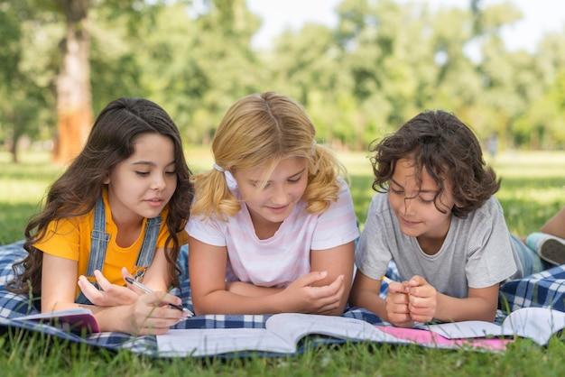 Kinder beim lesen im park