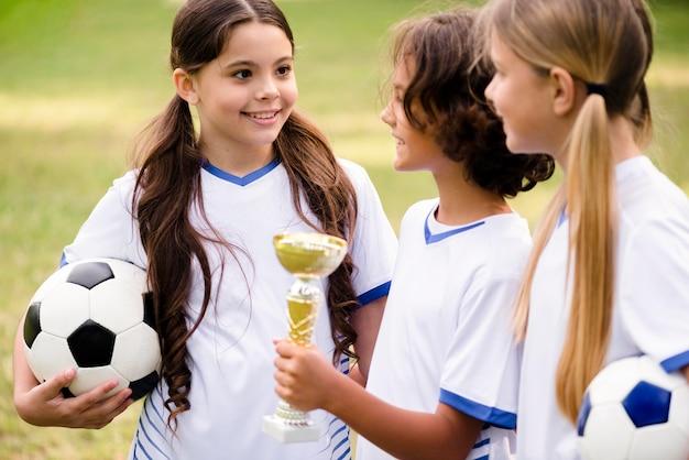 Kinder bekommen eine trophäe, nachdem sie ein fußballspiel gewonnen haben