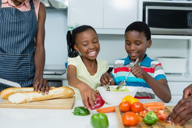 Kinder bereiten salat vor, während mutter brotlaib in der küche schneidet