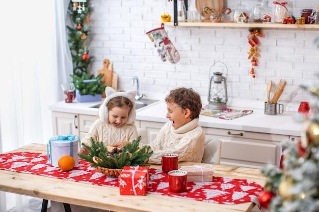 Kinder bruder und schwester in der küche feiern weihnachten. glückliche kinder am küchentisch öffnen geschenke. wunderbare momente des öffnens eines überraschungsgeschenks